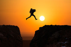 hikers-jumping-silhouette-man-off-cliff-direction-bright-sun-35850780